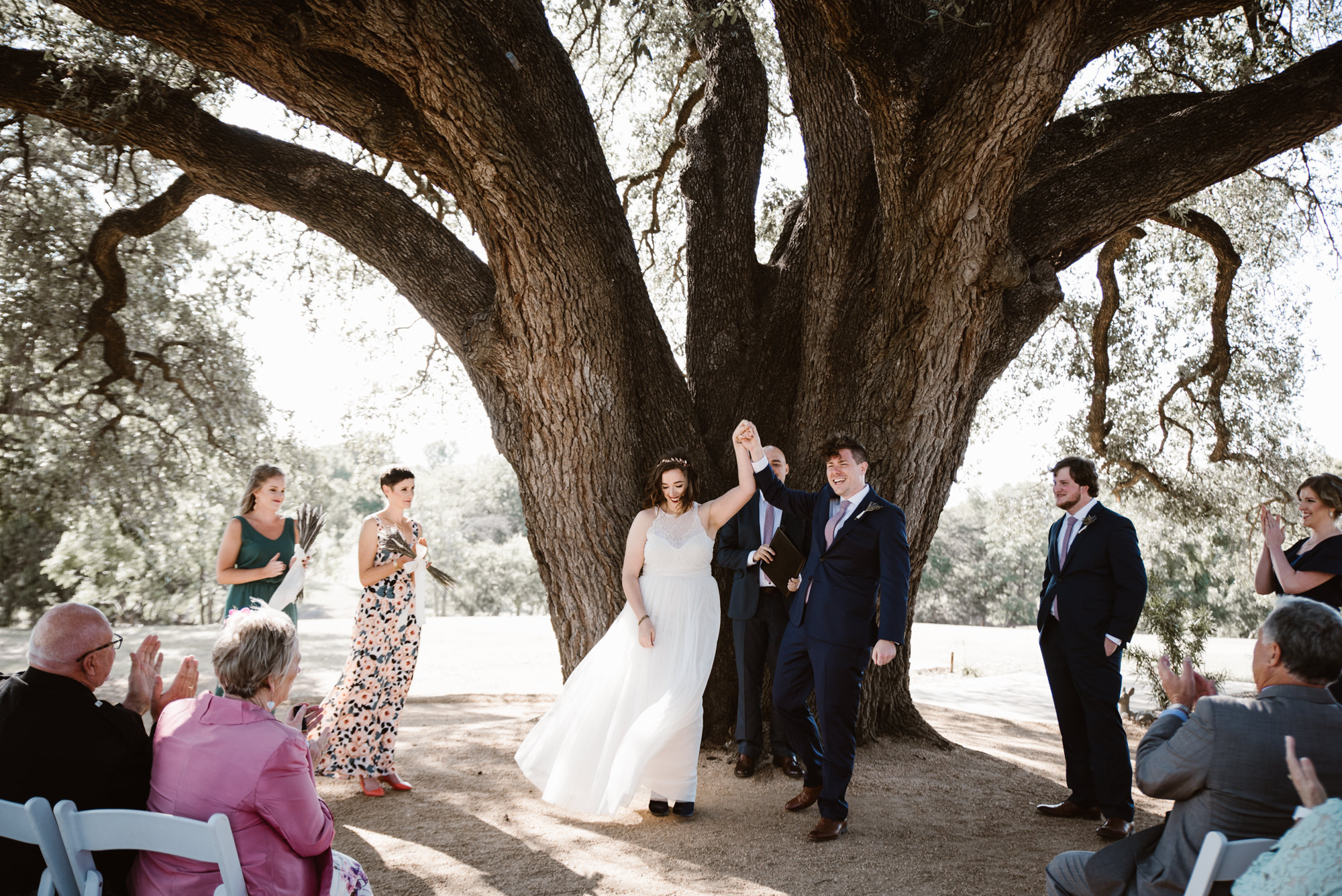 Texas Spring Wedding Ceremony At Stonebridge Venue Groom Holds Brides Hand Up In Excitement